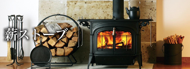 部屋に薪と薪ストーブが置かれており、薪ストーブの中は炎が燃えている様子。