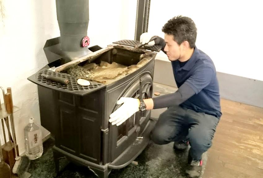 タニグチ商会の店主が薪ストーブの修理を行っている写真。