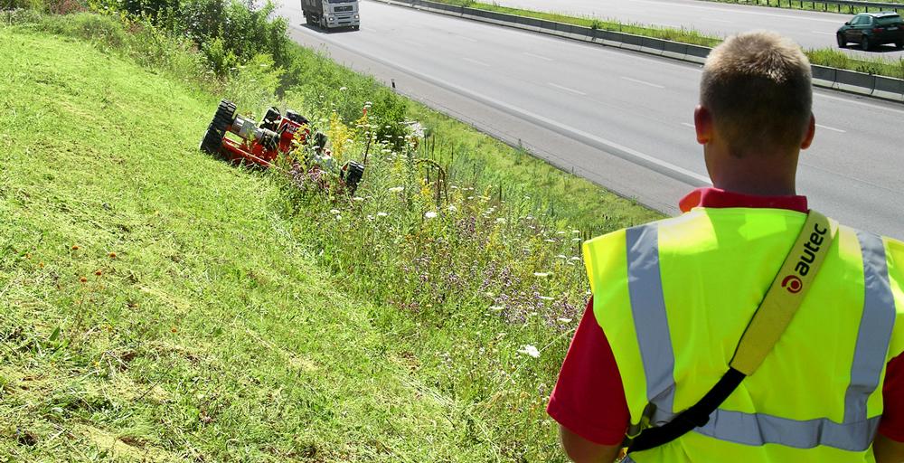 高速道路の横の草地をラジコン式草刈機で草刈りをしている様子。