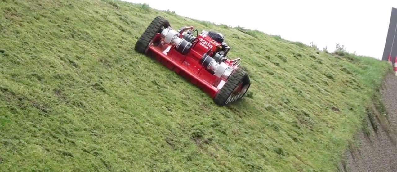 傾斜の強い場所をラジコン式草刈機で刈取っている様子。